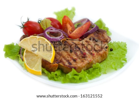 Grilled meat steak with herbs and tomatoes, onion, pepper, lemon, isolated on white background - stock photo