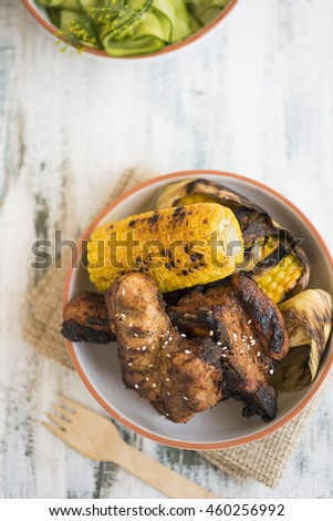 Grilled meat with corn on white table - stock photo