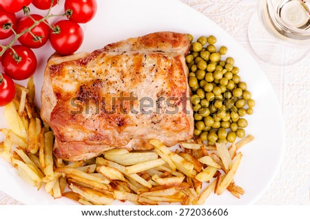 Grilled meat with French fries, vegetables and glass of wine, top view - stock photo
