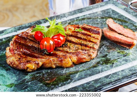 grilled meat with tomatoes on a marble tray - stock photo