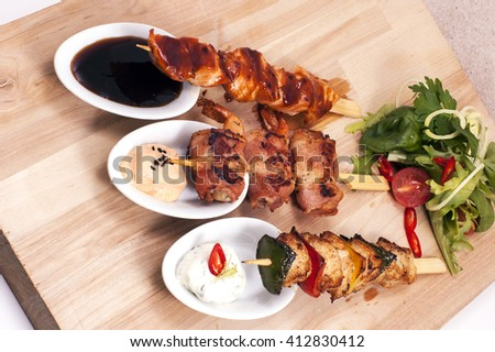 grilled meats of different kinds on wooden sticks with sauce and vegetables - stock photo
