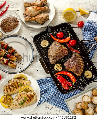 Grilled meats with vegetables on white wooden board. Top view