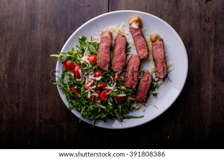 Grilled medium rare steak and some salad on the side - stock photo