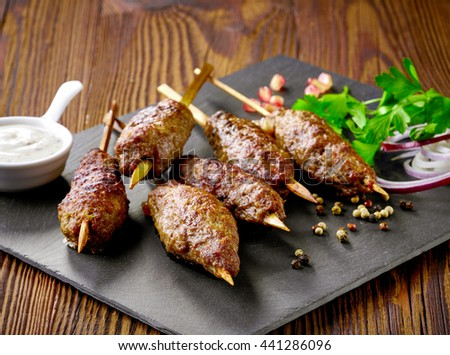 grilled minced meat skewers kebabs on wooden table, selective focus - stock photo