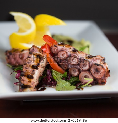 GRILLED OCTOPUS. Grilled octopus served with avocado puree and lemon oil  - stock photo