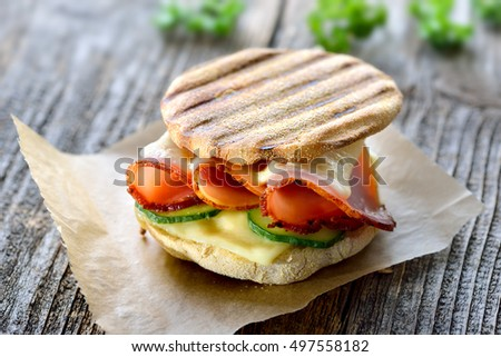 Grilled panini with ham, cheese and cucmber served on sandwich paper on a wooden table