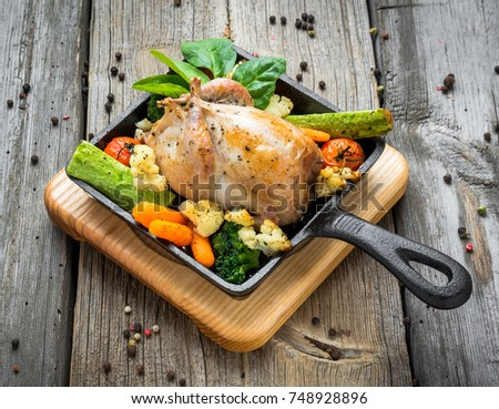 Grilled pheasant with bacon and spices and vegetables, on a wooden background