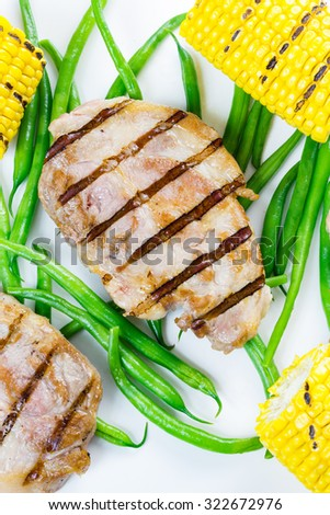 Grilled piece of pork with green beans and corn cobs, isolated on white background. - stock photo