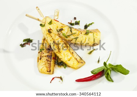 Grilled pineapple with honey and mint leaves