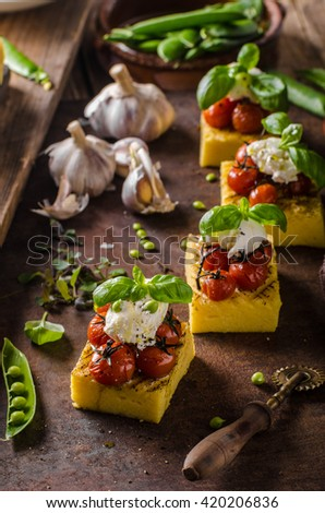 Grilled polenta with roasted tomatoes and creamy goat curd - stock photo