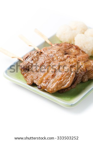 grilled pork and sticky rice on wooden background