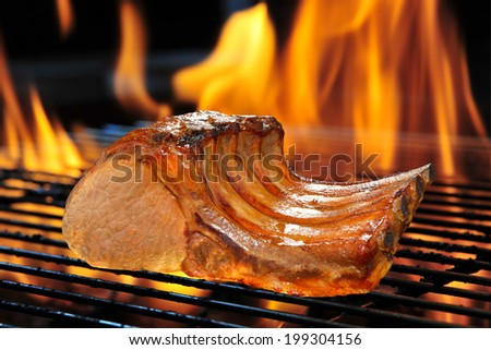 Grilled pork chop on the flaming grill.