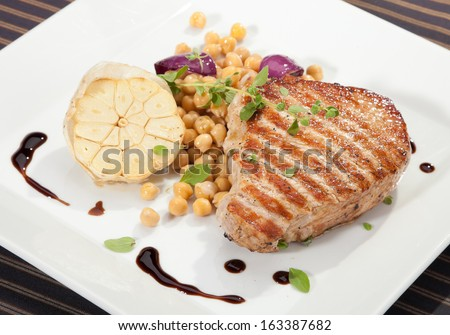 Grilled pork chop w peas and garlic slice