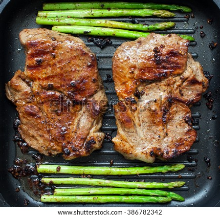 grilled pork chop with asparagus in pan - stock photo