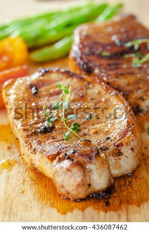 grilled pork chop with thyme and vegetable on wooden board