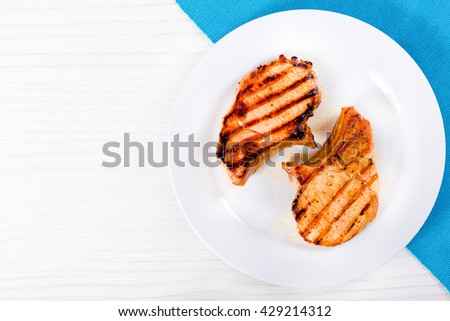 grilled pork chops on a white dish on a table, blank space left  top view - stock photo