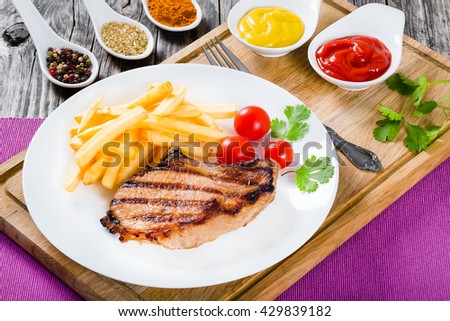 grilled pork chops on a white dish with french fries, cherry tomatoes, cilantro leaves and spices, on a wooden table, close-up