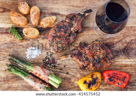 Grilled pork cutlets with vegetables and wine - stock photo