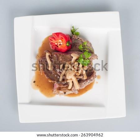 Grilled pork fillet with mushroom garnish - stock photo