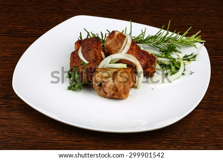 Grilled pork meat - shashlik with onion rings and rosemary