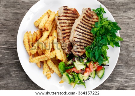 Grilled pork meat  with fried potatoes and vegetables. - stock photo