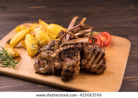 Grilled Pork Rib , Roast potatoes on wooden board with vegetables and potatoes . Pork ribs on wooden board with vegetables and potatoes . - stock photo