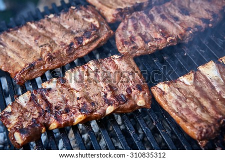 Grilled pork ribs on the grill. Shallow dof - stock photo
