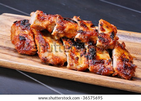 Grilled pork ribs on wooden plate - stock photo