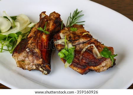 Grilled pork ribs with onion, parsley and rosemary