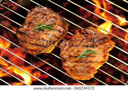 Grilled pork steak on the flaming grill - stock photo