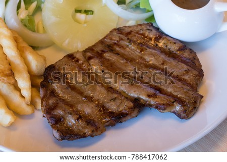 grilled pork steak with french fries and salad on table