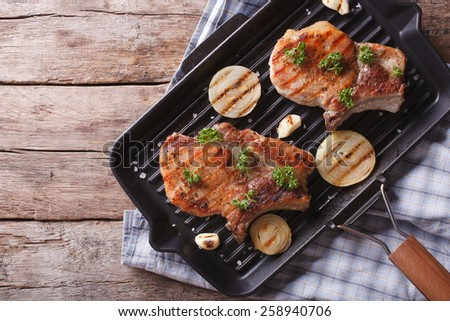 Grilled pork steak with onion in a pan grill, top view horizontal