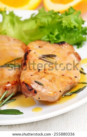 Grilled pork steak with orange sauce on white plate, close up view - stock photo