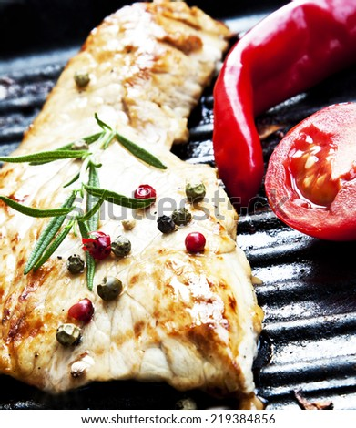 Grilled Pork Steak with Rosemary and Peppercorns, Red Chili Pepper and Tomatoes - stock photo