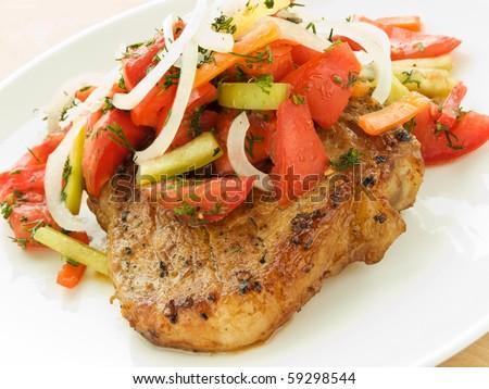 Grilled pork steak with vegetable garnish. Shallow dof. - stock photo