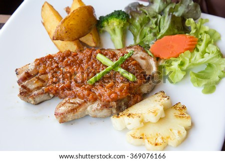 Grilled pork steaks, baked potatoes and vegetables.