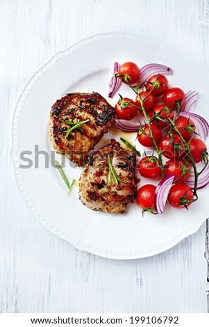 Grilled Pork Steaks with Cherry Tomatoes on a Plate - stock photo