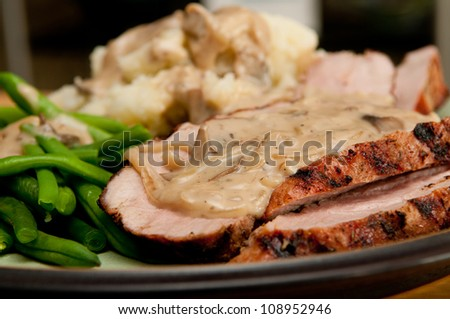 grilled pork tenderloin with a rich mushroom sauce, red skinned mashed potatoes and fresh green string beans - stock photo