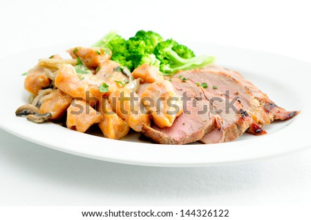 grilled pork tenderloin with sweet potato gnocchi and mushroom sauce - stock photo