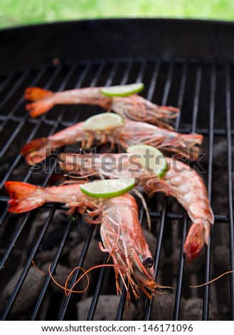 Grilled prawns on flaming grill.