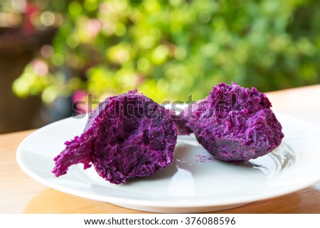 grilled purple sweet yam on white dish on wooden table