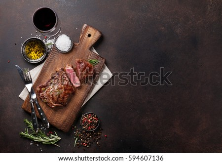 Grilled ribeye beef steak with red wine, herbs and spices. Top view with copy space for your text