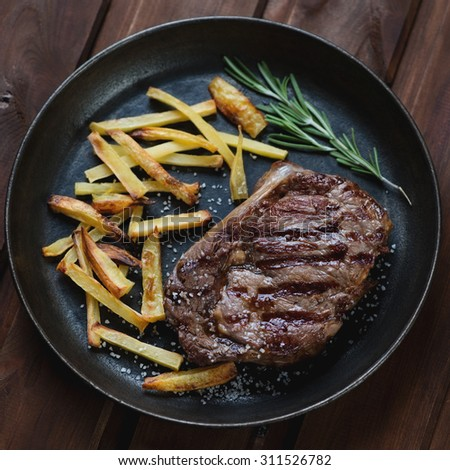 Grilled ribeye beefsteak with roasted potato in a frying pan
