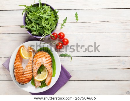 Grilled salmon and salad on wooden table. Top view with copy space - stock photo