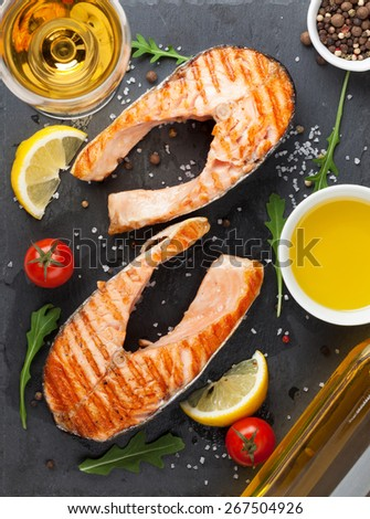 Grilled salmon and white wine on stone board. Top view - stock photo