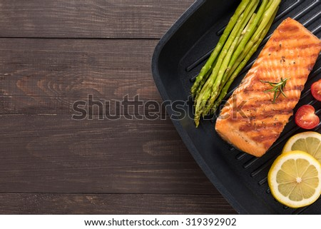 Grilled salmon cooked BBQ on a pan on wooden background. - stock photo