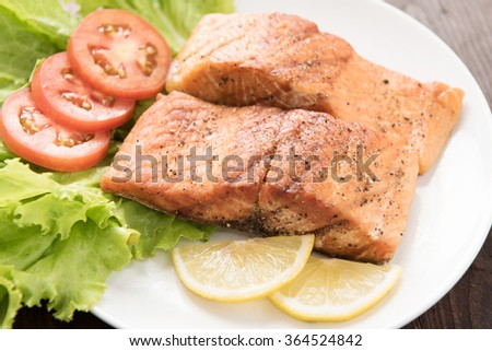 Grilled salmon fillet cooked BBQ and served with fresh herbs and lemon. - stock photo