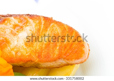 Grilled salmon fillet with roast potatoes. Macro. Photo can be used as a whole background. - stock photo