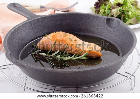 grilled salmon fillet with thyme, rosemary and olive oil in a cast iron pan - stock photo