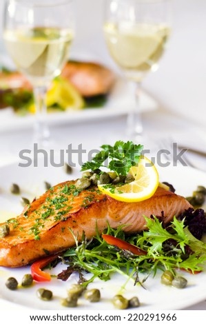 Grilled salmon fillet with vegetables and a glass of white wine. - stock photo